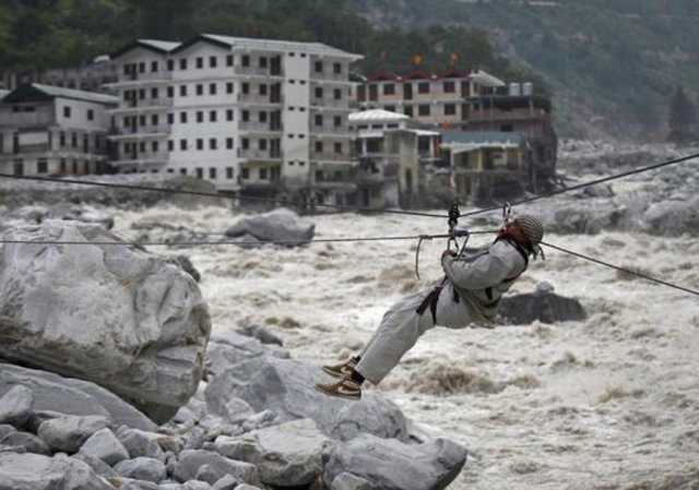 A man is pulled across to safety on a rope, as damaged buildings and the Alaknanda river are seen in the background, during a rescue operation in Govindghat in the Himalayan state of Uttarakhand, 23 June 2013. Photo: Danish Siddiqui / REUTERS