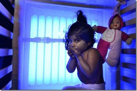 A inglesa Areesha Shehzad, de dois anos, que passa 12 horas por dia em cama com painéis que emitem raios UV em tratamento contra síndrome rara. (Foto: Caters)