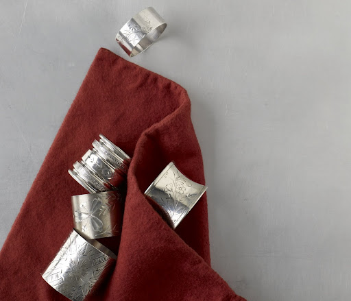 Bright-cut napkin rings bring a touch of brilliance to the dinner hour. By the 1870's, napkin rings had evolved from simple, unadorned bands to ovals, barrels, and octagons lavishly engraved with botanical patterns and other fanciful, minutely crafted designs.