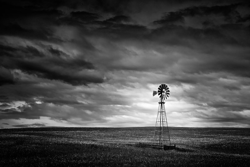 A majestic windmill stand tall undr a stormy sky north of Cochrane