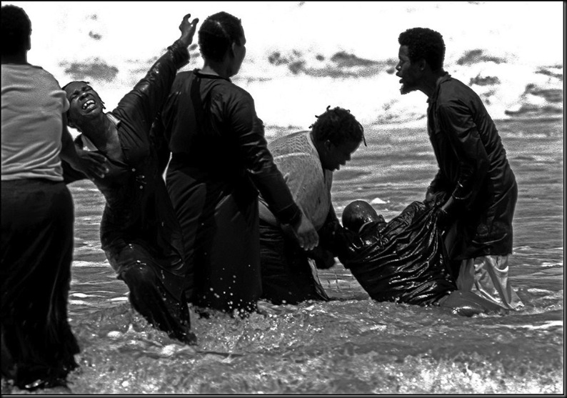 SOUTH AFRICA. Natal. Durban. Members of a religious group participating in a total immersion baptism ceremony in the Indian Ocean. 1984.