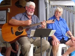 Member, Peter Wilton on guitar and fellow vocalist, Jeffrey, singing along.