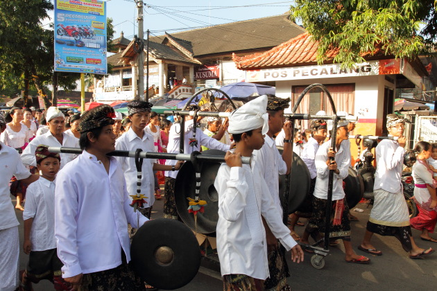 Balinese men play music during a procession at Ubud, Indonesia