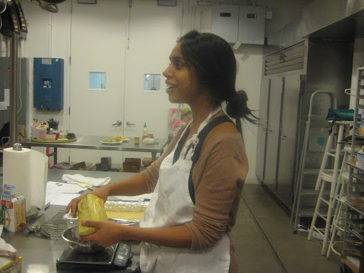 Sam Seneviratne getting into the spirit while she measures chocolate for her pecan bars.