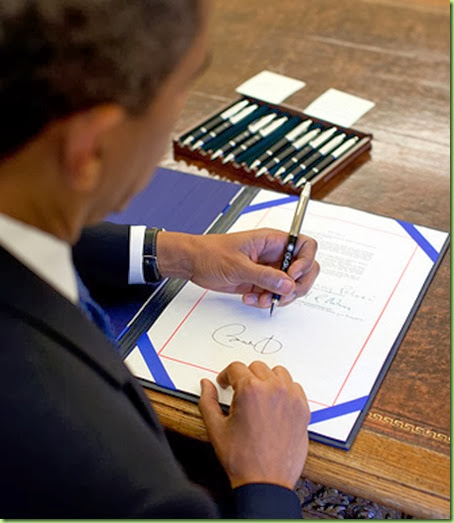 President Barack Obama signs a bill in the Oval Office,  August 7, 2009.    (Official White House Photo by Pete Souza)