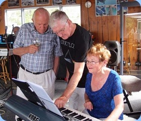 Diane Lyons playing and singing along as she uses the Korg Pa3X. Rob Powell and Gordon Sutherland help with the set-up for Diane as this is not her model of Korg. Photo courtesy of Dennis Lyons.