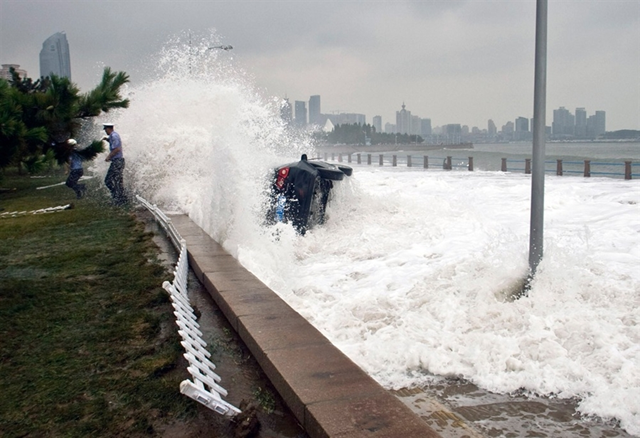 A car tipped over by a huge wave after its owner parked it on the bank to watch waves brought on by Typhoon Bolaven in Qingdao, 28 August 2012. AFP / Getty Images