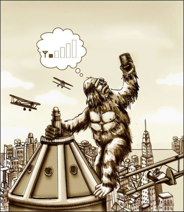 King Kong holds aloft a mobile phone, trying to get signal
