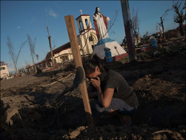 Marelom Cassanares, 37, who has five children and no home, cries at the grave of her husband in the aftermath of Super Typhoon Haiyan in Palo, on the outskirts of Tacloban, 16 November 2013. Photo: Nicolas Asfouri / AFP / Getty Images