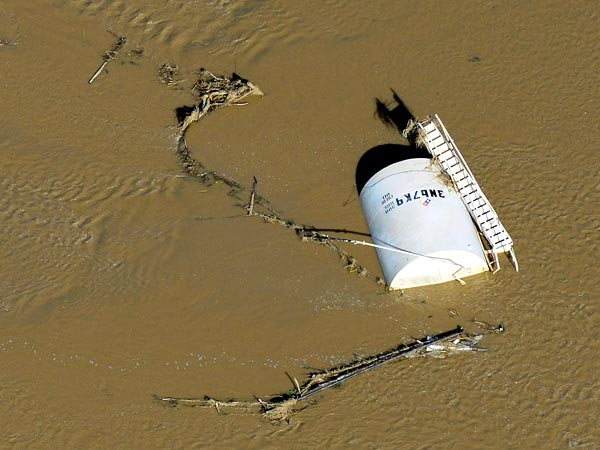 An overturned crude oil storage tank lies in the South Platte River on 17 September 2013. Hundreds of natural gas and oil wells, along with pipelines, were shut down by flooding. Photo: John Wark / AP