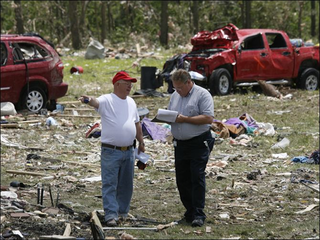 William White, left, speaks to his insurance agent Rick Anderson, from USAA, right, to asses the damage to his home and property that was destroyed by the tornado. White's truck, behind, was blown into their backyard. Photo: Amy E. Voigt / The Blade