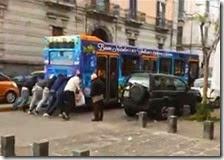 Un autobus viene spinto da alcune persone a Secondigliano