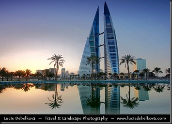 Bahrain - Sunrise next to Bahrain World Trade Center Reflected in Water Fountain - <br /><br />The Bahrain World Trade Center (also known as: Bahrain WTC or BWTC) is a 240 m (787 ft) high twin tower complex by South African architect Shaun Killa, located in Manama, Bahrain. The building is the first skyscraper in the world to integrate wind turbines into its design. The 50-floor structure is constructed next to the King Faisal Highway, close to popular landmarks such as the towers of BFH, NBB, Abraj Al Lulu and the scenic Pearl Roundabout. It is the second tallest building in Bahrain, after the twin towers of the Bahrain Financial Harbor.<br /><br />Three skybridges connect the towers; each holding one large wind turbine with a nameplate capacity of 225kW each, totalling to 675kW of wind energy production. These turbines, each measuring 29 m (32 yd) in diameter, face north, which is the direction from which air from the Persian Gulf blows in. The sail-shaped buildings on either side are designed to funnel wind through the gap to provide the maximum amount of wind passing through the turbines. This was confirmed by wind tunnel tests, which showed that the buildings create an 'S'-shaped flow, ensuring that any wind coming within a 45° angle to either side of the central axis will create a wind stream that remains perpendicular to the turbines. This significantly increases their potential to generate electricity. The wind turbines are expected to provide 11% to 15% of the towers' total power consumption, or approximately 1.1 to 1.3 GWh a year. This is equivalent to providing the lighting for about 300 homes annually.<br /><br />Camera Model: Canon EOS 5D Mark II, Lens's focal length: 17.00 - 40.00 mm, Photo Focal length: 20.00 mm, Aperture: 22, Exposure time: 0.8 s, ISO: 50<br /><br />All rights reserved - Copyright © Lucie Debelkova - www.luciedebelkova.com