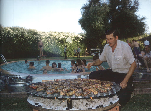 Summer isn't complete without a cookout by the pool. Garland of Garland Steel Company manning the grill at his pool party, Phoenix, Arizona, 1961. (Poolside With Slim Aarons, Abrams)