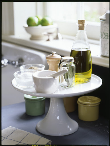A simple cake stand on a kitchen counter can keep everyday essentials neat and within easy reach.