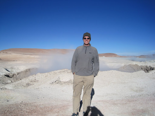 In front of one of the steaming geysers.