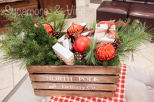 North Pole Delivery Company crate stuffed with gifts greenery and ornaments. A truly stunning Christmas Home Tour as part of the Christmas in the Country Blog Tour. This Plaid Inspired Country Christmas will knock your socks off. Features tours of the Living room, Dining Room and a Cocoa hot chocolate bar in the Breakfast room. There is so much inspiration for Christmas decorations in this one post. Be prepared to feel like you are cuddled up by the fire in a warm Northwoods comfy cottage! #country #Christmas #Plaid #Holiday decorating #Holiday ideas #Holidays #Christmas decor #Holiday decor