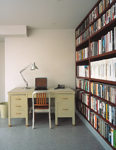A home office, the floor-to-ceiling bookcase, built from ecologically grown South American teak, was custom-made to fit the space.