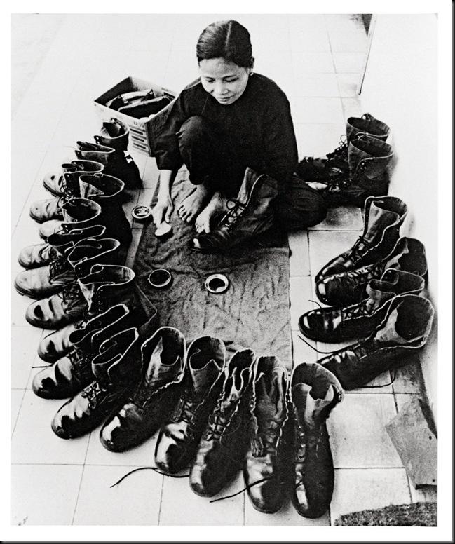 Donna Vietnamita lustrascarpe. Vietnam, circa 1973. Sembrano stivali militari statunitensi