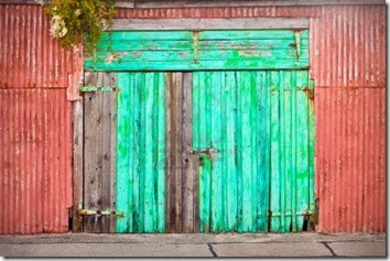 10401285-a-vibrant-turquoise-blue-door-in-a-metal-out-building