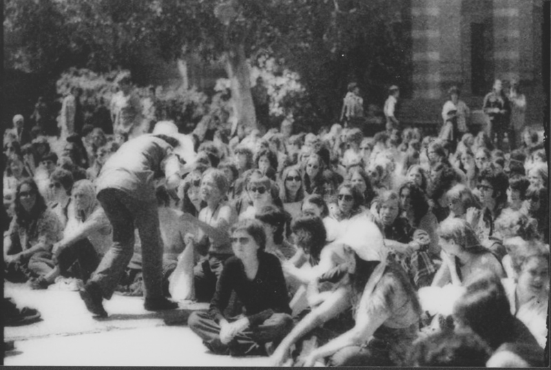 Women sit together on the grass in front of Janss Steps waiting for speeches at the First National Lesbian Conference, UCLA. April 14, 1973.
