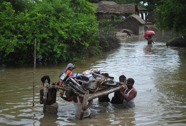 Pakistani villagers carry a motorbike on a bed frame through flood water following heavy monsoon rain at Golarchi town in Badin district, about 200 km east of Karachi, on 13 September 2011. Asif Hassan / AFP / Getty Images