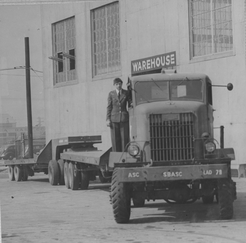 Dorothy Putnam standing by one of the trucks she drove during World War II. She was the only truck driver to win an Armed Forces Blue Star. 1945.