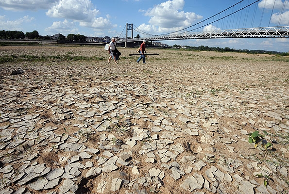 People walk across a dried riverbed in France. The spring of 2011 was France's driest in decades and hottest in a century, drying up reservoirs and killing crops. FRANK PERRY / AFP / Getty Images