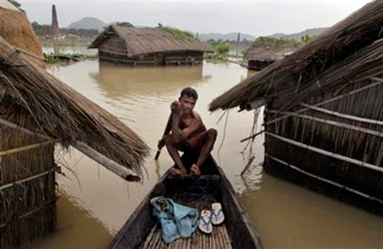 An Indian man rows his boat near submerged homes at Tin Tukra about 35 kilometers (22 miles) east of Gauhati, India, Saturday, 30 June 2012. Officials in northeastern India are on alert for poachers after surging flood waters forced endangered rhinos, Asiatic elephants, a variety of deer and other animals. Anupam Nath / AP Photo
