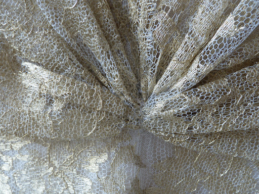 A close-up of the gold lace dress from Naeem Khan.