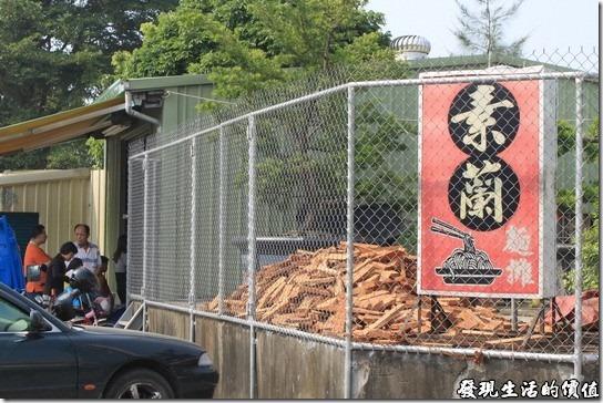 素蘭麵攤。『素蘭麵攤』的招牌,原本擺在下面,為了方便客人停車,所以把招牌移到了上頭,上面的木頭就是用來燒滷汁用的,放在那裡曬太陽,照片中依稀可以看到客人已經排隊排到外面來了。