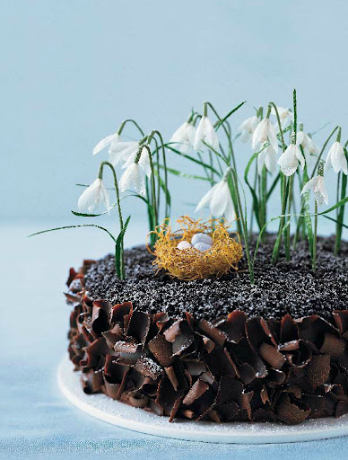 Crafted out of crepe paper, these dainty snowdrops crown a decadent soil—chocolate cake.