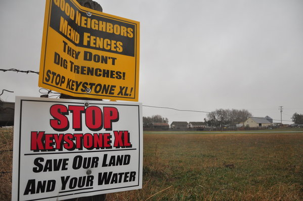 Signs are attached to a fence on the property of Jim Tarnick, a Nebraska farmer opposed to the Keystone XL pipeline project, 17 April 2013. Photo: Guillaume Meyer / AFP / Getty Images