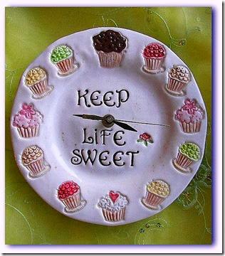 Imagem relógio de parede em formato de prato com decoração de cupcakes no luar dos números