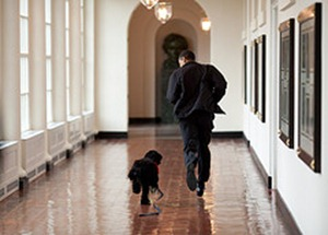 "March 15, 2009 ""The Obama family was introduced to a prospective family dog at a secret greet on a Sunday. After spending about an hour with him, the family decided he was the one. Here, the dog ran alongside the President in an East Wing hallway. The dog returned to his trainer while the Obama's embarked on their first international trip. I had to keep these photos secret until a few weeks later, when the dog was brought 'home' to the White House and introduced to the world as Bo."" (Official White House photo by Pete Souza)  This official White House photograph is being made available only for publication by news organizations and/or for personal use printing by the subject(s) of the photograph. The photograph may not be manipulated in any way and may not be used in commercial or political materials, advertisements, emails, products, promotions that in any way suggests approval or endorsement of the President, the First Family, or the White House."