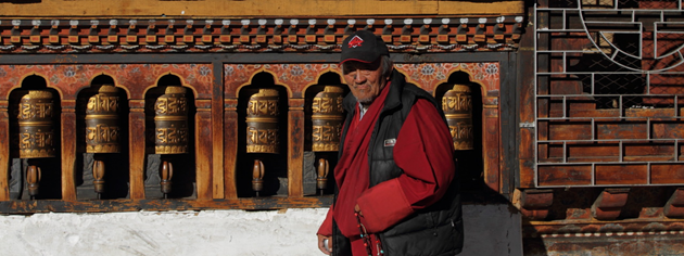 Buddhist devotee and the prayer wheels of Changangkha Lakhang, Thimphu, Bhutan
