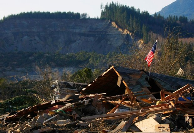 A flag sits atop what was Cory Kuntz and family's home Sunday, 23 March 2014. The family was at a baseball game Saturday morning when the fatal mudslide swept through the area, destroying everything on their property. The area where the land broke away is seen in the background. Photo: AP