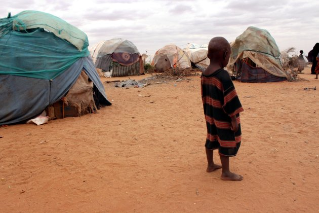 A barefoot child stands among ragged tents at a refugee camp in Dolo, Somalia on Wednesday, 18 July 2012. Photo: Jason Straziuso / AP Photo