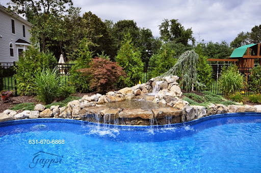Swimming Pool Waterfall Contractor <br /><br />http://deckandpationaturalstones.com/swimming-pool-Gunite-Vinyl-Fiberglass-Builders-long-island-ny.html<br /><br /><br />In this particular photo we come across a wonderful in ground swimming pool area having a waterfall in Yaphank, New York (11980). Surrounding this unique free-form in ground vinyl liner swimming pool area are many different varieties of landscaping. Each one of these unique variations of landscaping give this backyard a huge amount of color which generates a friendly welcoming atmosphere. The waterfall entering the swimming pool is an excellent feature to entertain your friends and relations you might have over in the warm summer seasonn. Not simply will the youngsters desire to have fun on your property all summer for your pool but the great swing set you observe in the background of the photo.http://deckandpationaturalstones.com/swimming-pool-Gunite-Vinyl-Fiberglass-Builders-long-island-ny.html