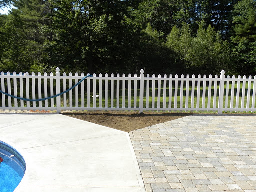 Planting bed enhances where pool plain concrete edging meets more decorative paver patio