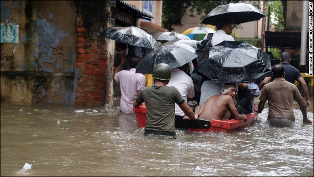 Indian police officials pull a boat through water-logged streets as they ferry residents to a safer place in Kolkata on 26 October 2013. Photo: Dibyangshu Sarkar / AFP / Getty Images