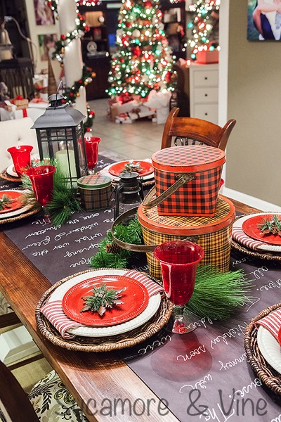 Red goblets white plates woven chargers greenery and lanterns make for an eclectic tablescape that wows you. A truly stunning Christmas Home Tour as part of the Christmas in the Country Blog Tour. This Plaid Inspired Country Christmas will knock your socks off. Features tours of the Living room, Dining Room and a Cocoa hot chocolate bar in the Breakfast room. There is so much inspiration for Christmas decorations in this one post. Be prepared to feel like you are cuddled up by the fire in a warm Northwoods comfy cottage! #country #Christmas #Plaid #Holiday decorating #Holiday ideas #Holidays #Christmas decor #Holiday decor