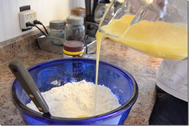 a woman pouring the egg mixture into the flour mixture