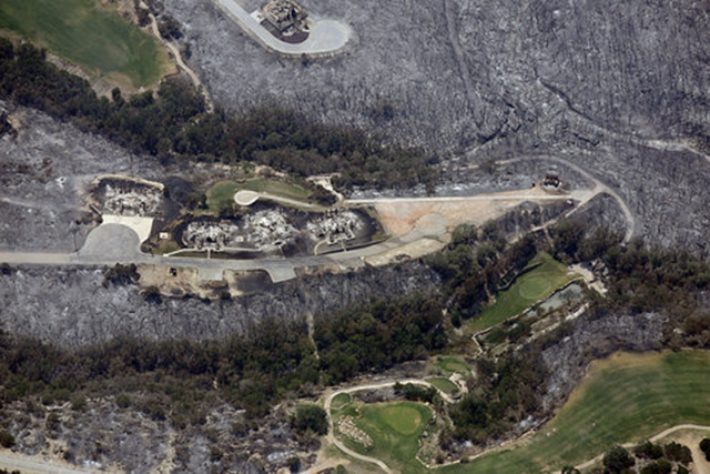 A golf course near Possum Kingdom Lake, Texas, is surrounded by burned-out homes and scorched grass and trees, 5 September 2011. McClatchy