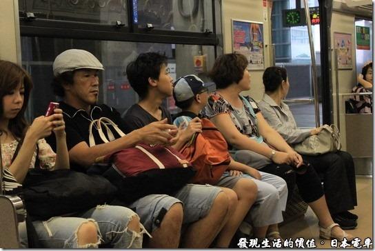 日本電車,車廂內的日本民眾幾乎是人手一隻手機,也不知道他們在看什麼內容,不過他們的手機幾乎清一色都是貝殼機。