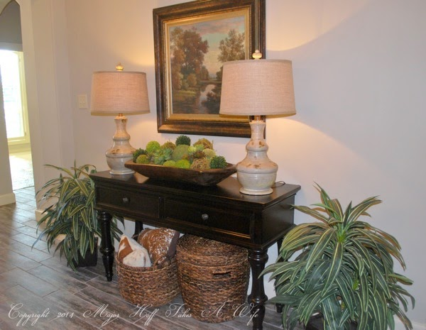 Entry way table with moss balls in french wooden dough bowl