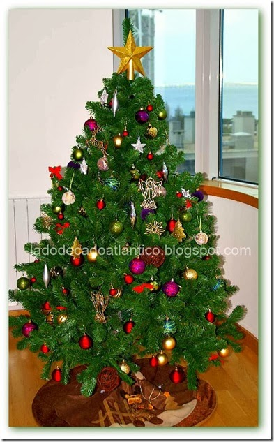 Imagem de um Pinheiro grande de Natal com muitos ornamentos e uma estrela dourada no topo