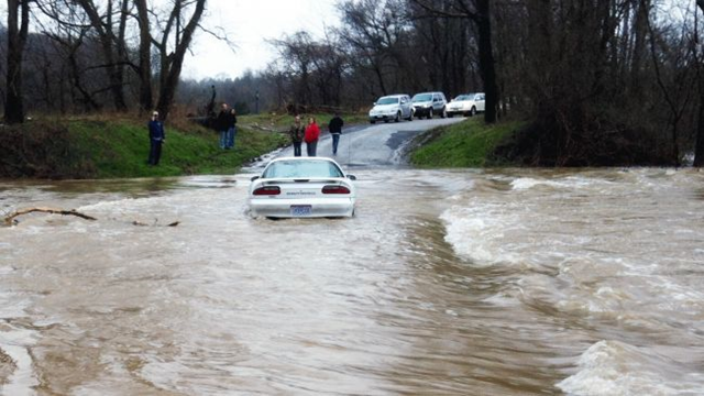 A car is stalled after trying to cross a flooded bridge over Saline Creek in Perry County, Missouri, on Sunday, 17 March 2013. Photo: Perry Sheriff / AP