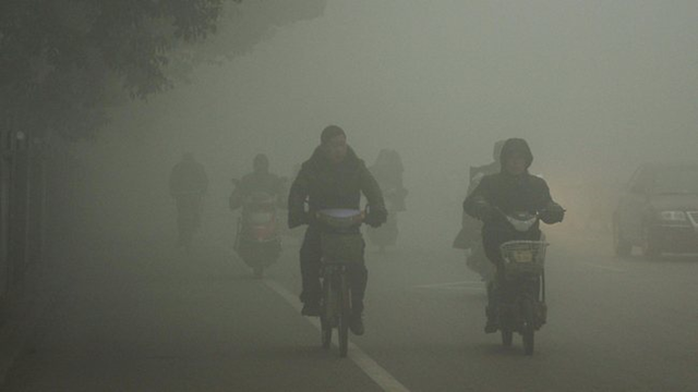 Cyclists travel on the road in Huaibei, in central China's Anhui province, through thick air pollution. China's reliance on coal reduces life expectancy by 5.5 years, says an MIT study. High levels of air pollution will cause 500 million people to lose an aggregate 2.5 billion years from their lives. Photo: Perth Now