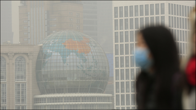 A woman wears a face mask on a hazy day in downtown Shanghai, in January 2015. China has ordered a popular anti-pollution film, 'Under the Dome', removed from major online outlets. In Xi'an, two people who had protested against smog were reportedly detained on 9 March 2015. Photo: ALY SONG / Reuters / Landov